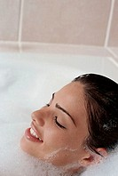 High angle view of a young woman taking a bubble bath