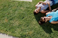 High angle view of a young couple lying on the grass