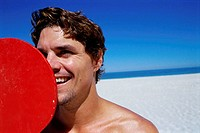 Close-up of a young man smiling on the beach