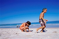 Side profile of a brother with his sister playing leapfrog on the beach