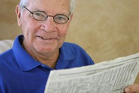 Portrait of a senior man reading a newspaper