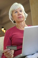 Low angle view of a senior woman sitting in front of a laptop holding a credit card