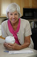 Portrait of a senior woman holding a piggy bank smiling