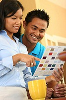 Close-up of a young couple choosing color from a color swatch