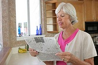 Close-up of a senior woman reading a newspaper