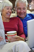 Close-up of a senior couple sitting on a couch looking at a laptop