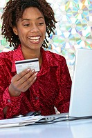 Young woman sitting in front of a laptop holding a credit card