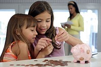 Two sisters looking at a coin with their mother standing in the background