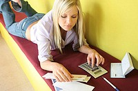 High angle view of a young woman lying on a bench with bills and a calculator in front of her