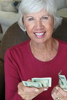 Portrait of a senior woman holding money