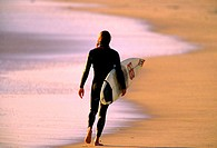 Surfer walking along the beach