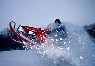 Side profile of a man riding a snowmobile (thumbnail)