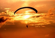 Silhouette of a person paragliding at dusk