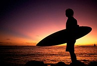 Silhouette of a young man holding a surfboard on the beach