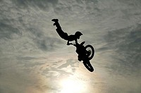 Silhouette of a man performing stunts on a motorcycle