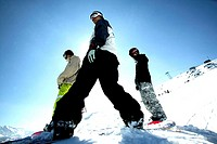Low angle view of three people snowboarding