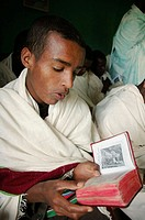 Young seminarian reading religious prayer book at an orthodox seminary in Ambo. Ethiopia