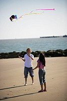 A young couple flying a kite on a beach