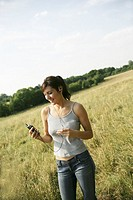 A girl standing in a field listening to music on a MP3 player