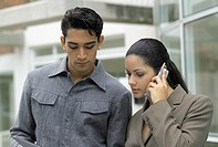 Young businessman and young businesswoman, woman on the phone, outdoors, close-up