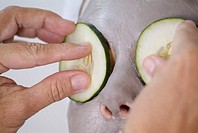 A woman with a face pack and cucumber slices on her eyes