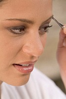 Woman applying eye shadow, close-up