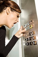 A young woman in elevator pressing buttons