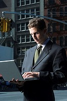 Businessman using laptop in street