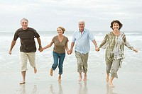 Four senior adults running along a beach