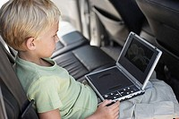 Boy sat in car with portable dvd player