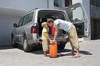 Father and son putting suitcases in car