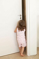 Young girl pushing open a door