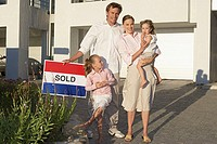 Family stood outside house holding sold sign