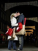 Couple kissing whilst christmas shopping