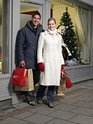 Mid adult couple walking out shop