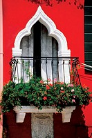 Red and pink flowers on a balcony, Burano, Venice, Italy