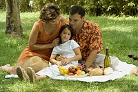 Portrait of couple and child having a picnic in the park
