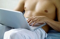 Man working on laptop at home, close-up