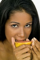 Portrait of a young woman eating a sliced grape fruit