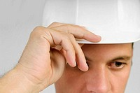 Man in hardhat with hand on hat obscuring part of face, close-up