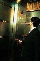 Businessman pushing buttons in elevator