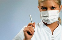 Portrait of a female doctor wearing a surgical mask and holding a pen