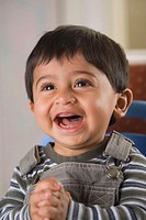 Close-up of a baby boy laughing with his hands clasped