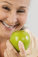 Smiling senior woman holding green apple