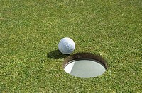 Golf ball near hole, close-up