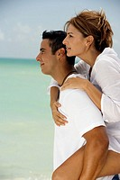 Side profile of a young woman riding piggyback on a mid adult man on the beach