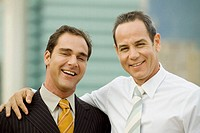 Portrait of two businessmen standing and smiling