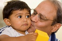 Close-up of a grandfather kissing his grandson