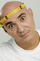 Portrait of a mid adult man holding a measuring tape around his head