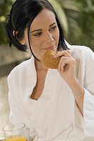 Young woman wearing terrycloth robe and holding muffin and orange juice outdoors, close-up